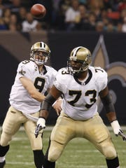 New Orleans Saints quarterback Drew Brees (9) throws a pass as guard Jahri Evans protects him against the New York Giants during a 2009 game. The Saints released Evans Monday.