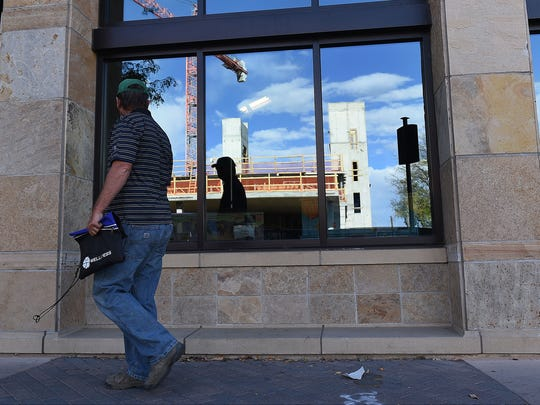 Construction on the Elizabeth Hotel is reflected in a window across the street in Old Town Fort Collins on October 5, 2016.