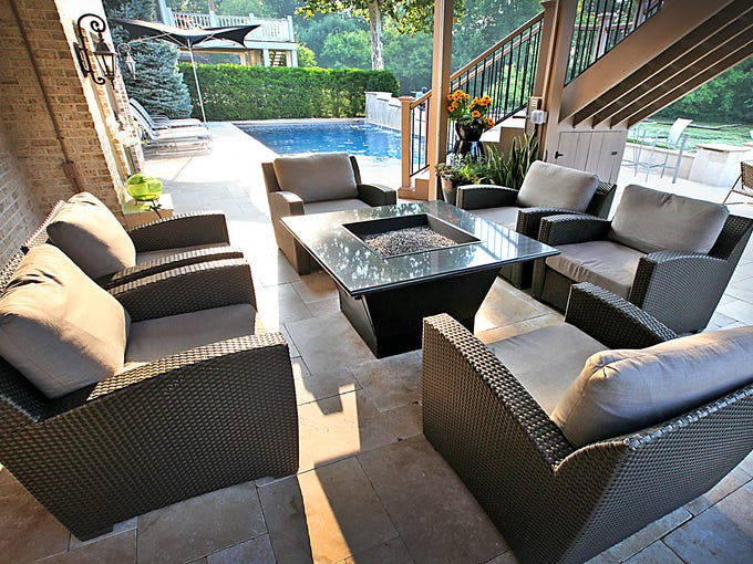 Heavy yet comfortable outdoor wicker seating is situated around the fire pit, under the cover of the second-level deck at the Geist home of Joan and Randy Steenbergen. It was purchased at Especially Wicker in Castleton.
