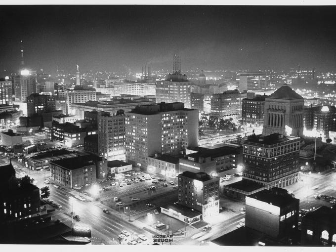 This view from 30 stories up at Riley Center was captured in a half-second exposure on July 26, 1963. Looking southwest toward Downtown with North Delaware and East Michigan Street in the foreground. Some buildings pictured have been demolished, such as the Knights of Pythias building (lower center at left) and surrounding smaller buildings, removed for INB tower (One Indiana Square); Architects Building(left center), now American Building and part of Indianapolis Newspapers; the Essex House (now a parking lot); Indiana Bell telephone building (shown behind Essex House with antennas on top), now Ameritech. World War Memorial is at right in center. Shown at left in a distance are the Merchants Bank Building  (with radio antenna) and the Soldiers and Sailors Monument. A present day skyline view would include several tall structures including the Bank One Tower, RCA Dome and AUL Building. Photo by Indianapolis News photographer Bill Palmer