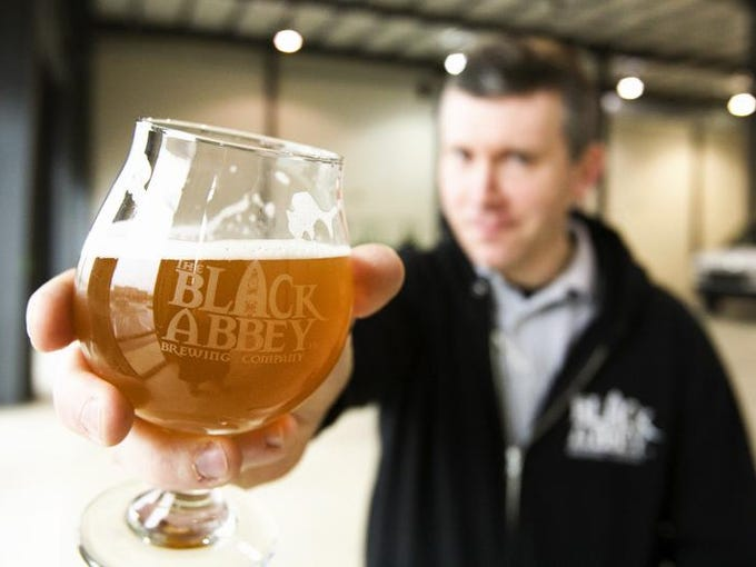 Carl Meier, founder of The Black Abbey Brewing Co., holds a glass of his brewery's beer.