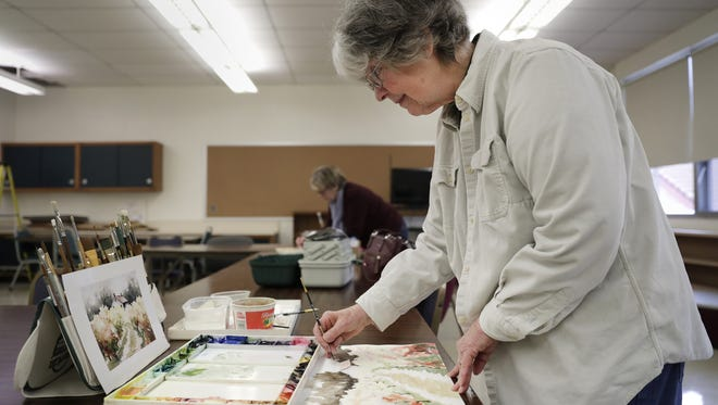 Irena Copeland works on a painting Thursday at the former St. Bernadette School, which has been transformed into the Thompson Center on Lourdes while options are explored for a new senior center in Appleton.