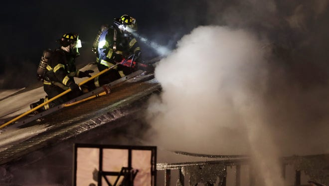 Firefighters from the Little Chute Fire Department work to cut through the roof on the scene of a structure fire Monday in Little Chute.