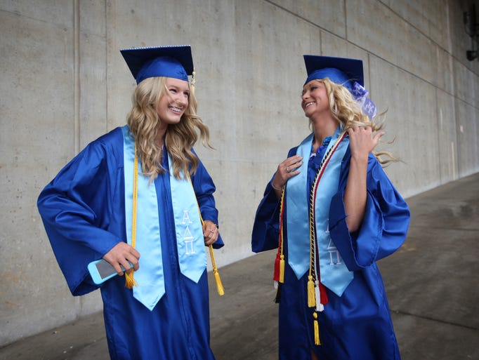 Taryn Adams, left, of Richmond, Ky. and Jillian Rengel of Sandusky, Ohio prep themselves while waiting to meet up with a friend at the University of Kentucky's 147th May Commencement at Rupp Arena in Lexington, Ky. Both women were graduating with bachelors of science in human nutrition. May 10, 2014.