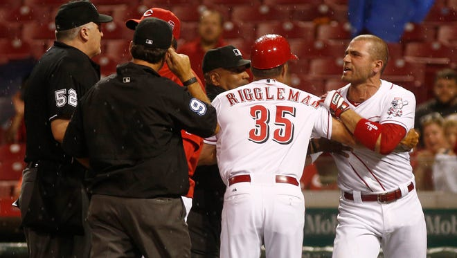 Cincinnati Reds first baseman Joey Votto (19) is restrained by third base coach Jim Riggleman (35) after Votto was ejected from the game against the Pittsburgh Pirates in the eighth inning at Great American Ball Park.