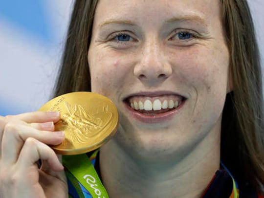United States' Lilly King shows off her gold medal