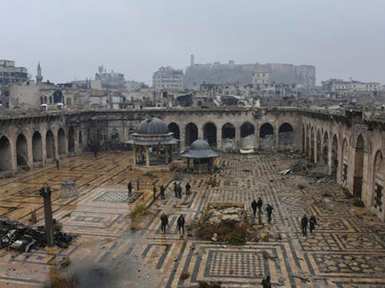 This photo released by the Syrian official news agency SANA, shows Syrian troops and pro-government gunmen marching walk inside the destroyed Grand Umayyad mosque in the old city of Aleppo, Syria, Tuesday, Dec. 13, 2016. Government forces and rebel fighters have fought to control the 12th century mosque in the last four years, until Syrian troops seized control of it this week. Syrian rebels said Tuesday that they reached a cease-fire deal with Moscow to evacuate civilians and fighters from eastern Aleppo, after the U.N. and opposition activists reported possible mass killings by government forces closing in on the rebels' last enclave.
