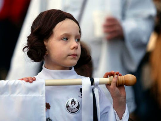 """Addy Longlois, 7, dressed as Princess Leia, walks in a parade in honor of actress Carrie Fisher, who played Princess Leia in the """"Star Wars"""" movie series, in New Orleans, Friday, Dec. 30, 2016. Fisher died on Dec. 27, 2016, at the age of 60. The parade was held by the Krewe of Chewbacchus, a """"Star Wars"""" themed Mardi Gras Krewe."""