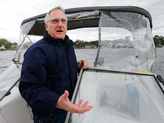 """In this Friday, April 7, 2017 photo, John J. Korte gestures as he points out oyster cages along a sand bar in Back Bay waterway in Virginia Beach, Va. As the shellfish makes a comeback, a modern-day oyster war is brewing, between wealthy waterfront property owners and working-class fishermen. """"All of sudden you have people working in your backyard like it was some industrial area,"""" said Korte."""