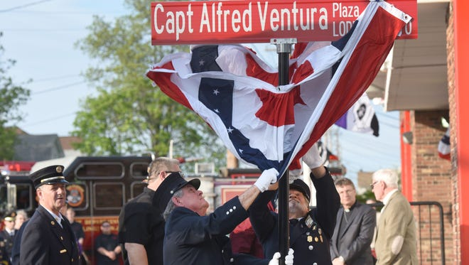 Firefighters Ken Doviak and Richard Kapusta unveil the sign as Wallington Fire Department dedicated the Johnson Ave Fire House to Al Ventura who died in the line of duty battling a fire in 1970