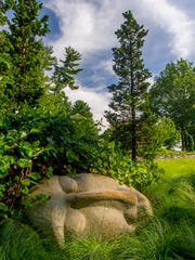 CAPTION: A face boulder by the sculptor Marcia Donahue looks restful sleeping at the base of the Ruin Meadow.