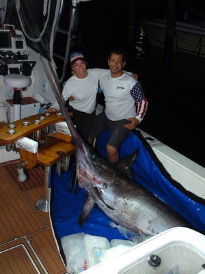 Jessika Harvey and Rush Rashidi of North Palm Beach pose aboard their boat the Wahuka with this impressive swordfish they hooked while fishing off Palm Beach County and boated 24 hours and 83 miles later off of Vero Beach.