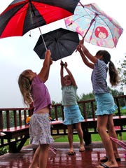 Ella Simmons, 5 at left, Abby Simmons, 7 center, and Katie Riveros, 8 at left of Queens, N.Y, play with umbrellas in the morning drizzle in July 2007. Through the Fresh Air Fund Katie had spent the previous three summers with the Simmons family, of St. Albans.