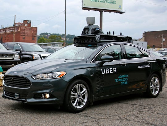 A self driving Uber car drives down River Road on Pittsburgh's