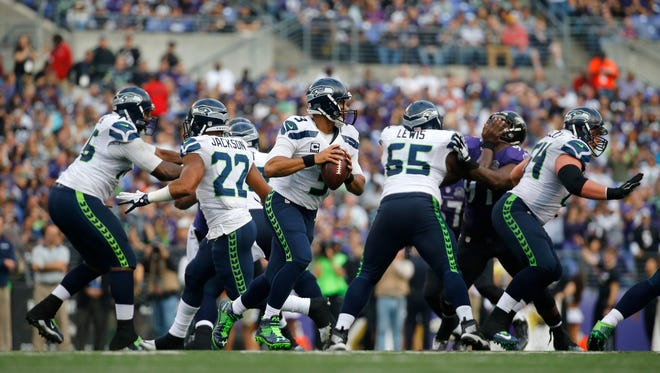 Seattle Seahawks quarterback Russell Wilson, center, looks for a receiver during an NFL football game against the Baltimore Ravens, Sunday, Dec. 13, 2015, in Baltimore.