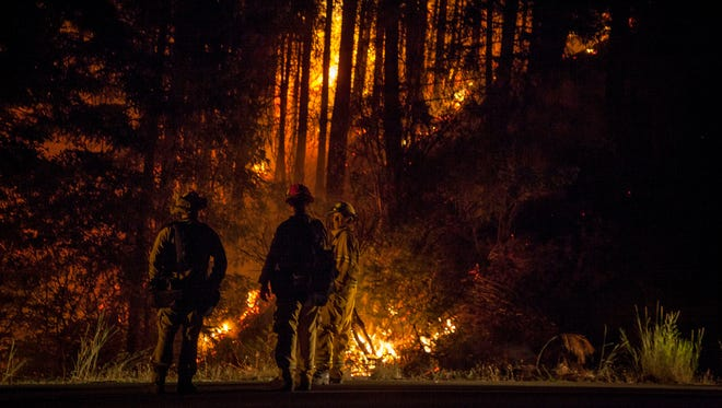 A Cal Fire firefighter, makes his way through the terrain after setting a backfire to burn excess fuel and make progress on the Carr Fire as it burns into the evening along Highway 299, just east of the Trinity County line in California on July 30, 2018. Firefighters made progress with the fire, which was over 20 percent contained by the evening.