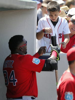 Boston Red Sox's David Ortiz (34) hands a bat to a young fan after autographing it before going out for his at-bat in the fifth inning of a spring training baseball game against the Boston Red Sox on Thursday, March 31, 2016, in Fort Myers, Fla. (AP Photo/Tony Gutierrez)