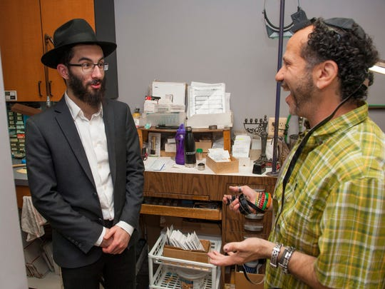 Lubavitch Yeshiva student Chaim Polter, left, of Oak Park speaks with jewelry store co-owner Robert Weinberger of Oak Park in the back room of Emery Creative Jewelers in Farmington Hills on Friday, July 21, 2017. Polter visits Jewish business owners on Friday to perform mitzvahs, wrap tefillin and say prayers.