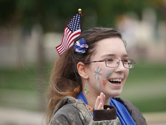 Thousands attended and participated in the Veterans Day Parade in Springfield, MO on Sat. Nov. 5, 2016. Amelia Cuevas, 15, waves to the veterans.