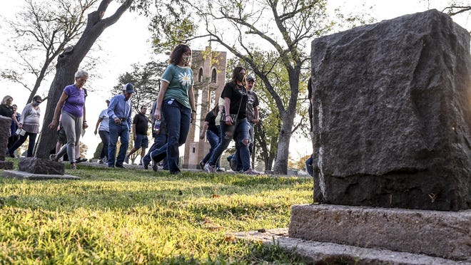 A group of patrons make their way to the next re-enactor Friday through a portion of Valley View Cemetery during one of the Finney County Historical Society's annual Historic Walking Tour of the cemetery.