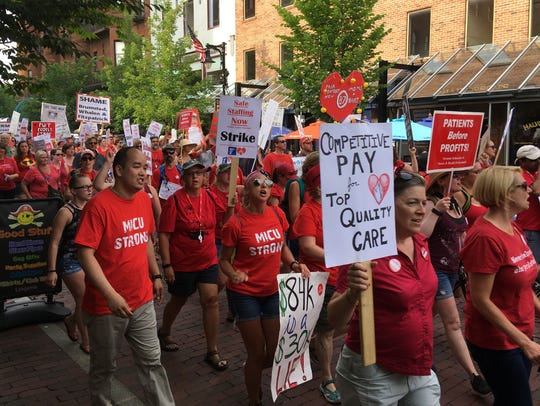 Hundreds of striking nurses from the UVM Medical Center and their supporters march into downtown Burlington Friday night, July 13, 2018.