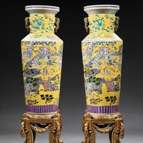 This 60-inch-high pair of Chinese clobbered famille rose porcelain vases from the 19th or 20th century sold for $4,780 at Neal auction in New Orleans recently. They have multicolored decorations and a yellow ground.