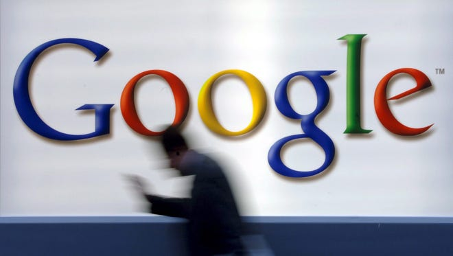 A man passes the Google logo as he reads.