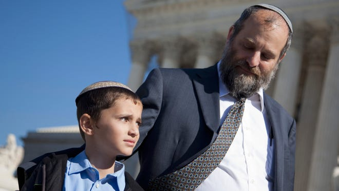 Menachem Binyamin Zivotofsky with his father, Ari, outside the Supreme Court in November 2011.