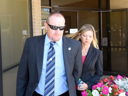 Bull Shoals Police Chief Dan Sutterfield and his wife, Andrea, leave the federal courthouse in Harrison on July 15. Sutterfield would resign as Bull Shoals police chief, making a deal with federal prosecutors to never work in law enforcement again.
