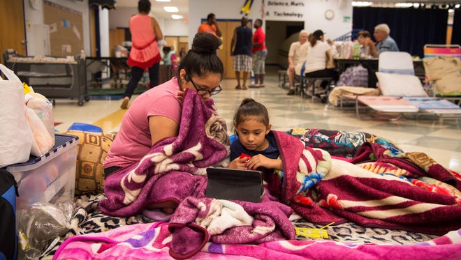 Daniela Torres, 14, and little sister Priscila Torres, 7, both of Stuart, stream a show at the shelter at J. D. Parker Elementary School in Stuart on Saturday, Sept. 9, 2017, ahead of Hurricane Irma.