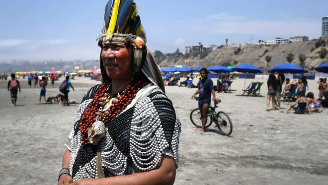 A man from Peru's Ashaninka indigenous community stands on Agua Dulce beach before a gathering that's part of the Climate Change Conference in Lima, Peru, on Dec. 6.