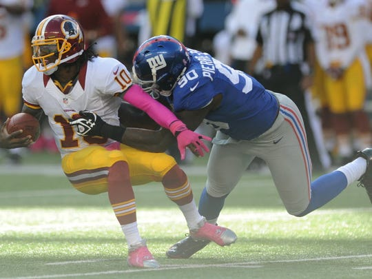 Robert Griffin III of the Redskins is tackled by Jason Pierre-Paul of the Giants in an October 2012 game at MetLife Stadium in East Rutherford.