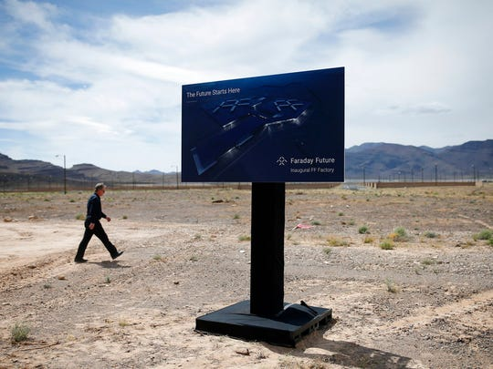 In this April 13, 2016, file photo, a man walks by a sign at an event to mark the start of construction for Faraday Future in North Las Vegas, Nev. Electric car maker Faraday Future said Monday, July 10, 2017 that it is deserting its plan to construct a $1 billion manufacturing plant in southern Nevada eight months after suspending the project and sinking at least $120 million into it.