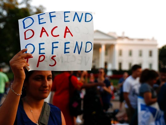 """A woman holds up a sign that reads """"Defend DACA Defend TPS"""" during a rally supporting Deferred Action for Childhood Arrivals, or DACA, outside the White House in Washington, Monday, Sept. 4, 2017."""