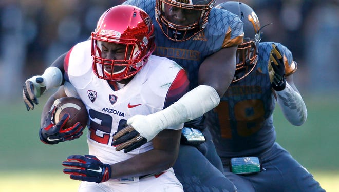 Arizona running back Nick Wilson is tackled by Arizona State linebacker Christian Sam during the Territorial Cup game at Sun Devil Stadium in Tempe on November 21, 2015.