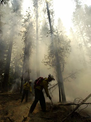 Firefighters Todd Ostendorp, front, and Mike Blatner, back, work the fireline of a wildfire near the U.S. Forest Service lookout at Round Mountain, near Lapine, Ore., Monday, Aug. 13, 2001.