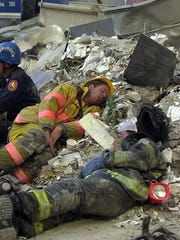 Exhausted  firefighters rest amid the rubble at Ground