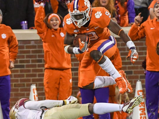 Clemson running back Travis Etienne (9) leaps over Florida State defensive back Tarvarus McFadden (4) during the fourth quarter in Memorial Stadium at Clemson on Saturday.