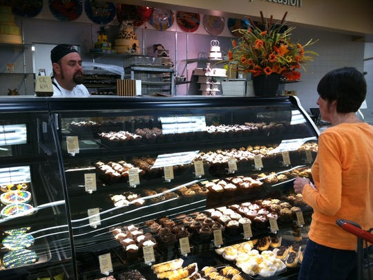 A customer looks over the gourmet cupcake choices at the Hy-Vee on South Minnesota Avenue.