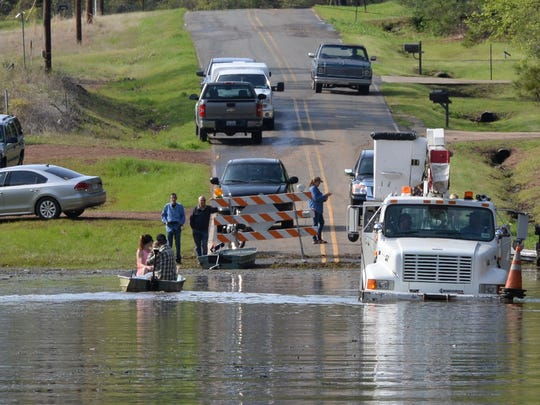 A Southwestern Electric Power truck makes it's way into deep water that has stranded many residents along Caddo Lease Road at Caddo Lake.