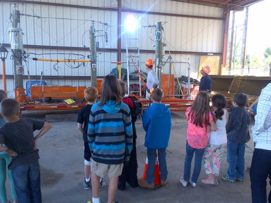 Kevin Hardesty, a NYSEG line mechanic first class, shows students the danger of a ladder or other conductor making contact with a live power line. Fred Casterline, NYSEG line mechanic first class, is at right.