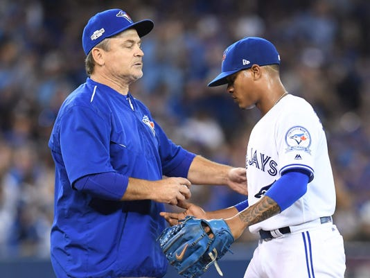 Toronto Blue Jays starting pitcher Marcus Stroman, right, hands the ball to manager John Gibbons as he leaves the game during sixth inning game three American League Championship Series baseball action against the Cleveland Indians in Toronto on Monday, Oct. 17, 2016. (Frank Gunn/The Canadian Press via AP)