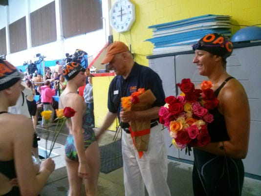 Nick Giovanni is presented flowers during a ceremony honoring his 20 years of volunteerism for the Olympic Aquatic Club in Bremerton (Courtesy photo)