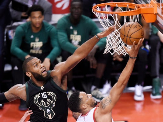 Toronto Raptors guard Norman Powell (24) is fouled by Milwaukee Bucks center Greg Monroe (15) as he drives to the basket during the second half in Game 5 of a first-round NBA basketball playoff series in Toronto on Monday, April 24, 2017. (Nathan Denette/The Canadian Press via AP)