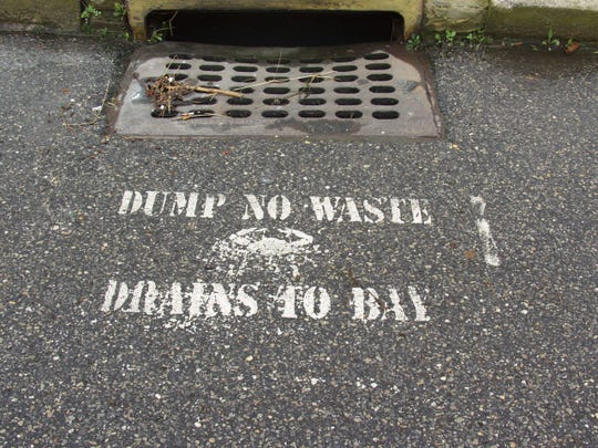 """A message near a storm drain in Seaside Park reminds people to """"Dump no waste"""" because whatever goes in """"Drains to (Barnegat) Bay."""""""