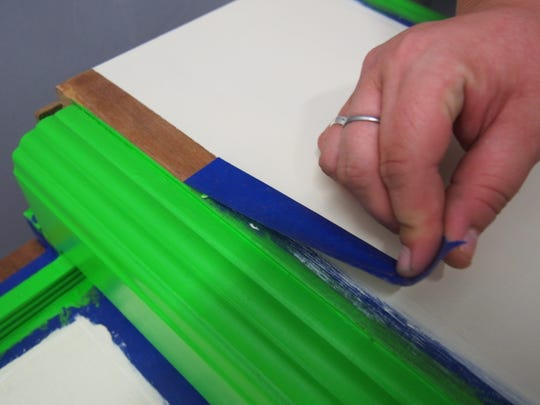 Artist Breana Whitlock uses tape to help color block a design on a piece of furniture.
