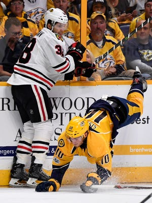 Predators center Colton Sissons (10) tumbles to the ice in front of Blackhawks left wing Ryan Hartman (38) in the first period of Game 3 in the first-round NHL playoff series last season.