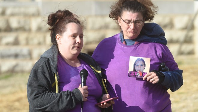Nicole Brakebill speaks Tuesday evening while her mother Loretta Russell holds up a picture of her sister Kirstie Headley who was stabbed to death last week by her estranged husband. AThe women were attending a vigil hosted by the domestic violence shelter Serenity in honor of Kirstie.
