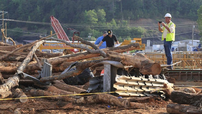 Investigators look over the scene of a double fatality accident Monday in Clinton. Officials said a log truck lost control and slid onto a bridge under construction killing two and injuring more than 20 workers on the bridge.