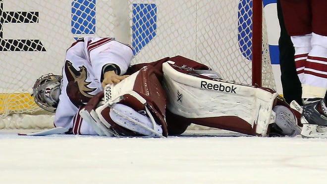 Goaltender Mike Smith of the Phoenix Coyotes leaves the game against the New York Rangers after being injured in the third period at Madison Square Garden on March 24, 2014 in New York City.